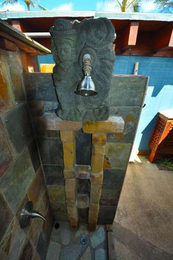 Outdoor bathroom with stone carved figure at shower head thumb