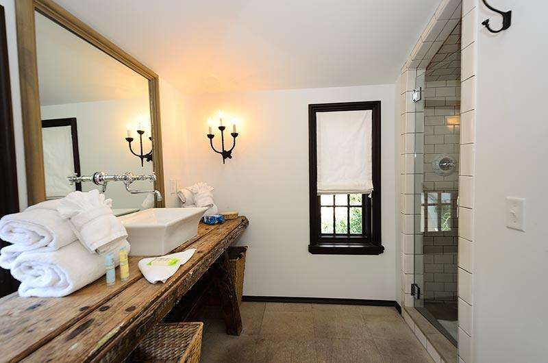 Master bathroom with antique farm table serving as the counter, large walk in shower with dual rain shower heads