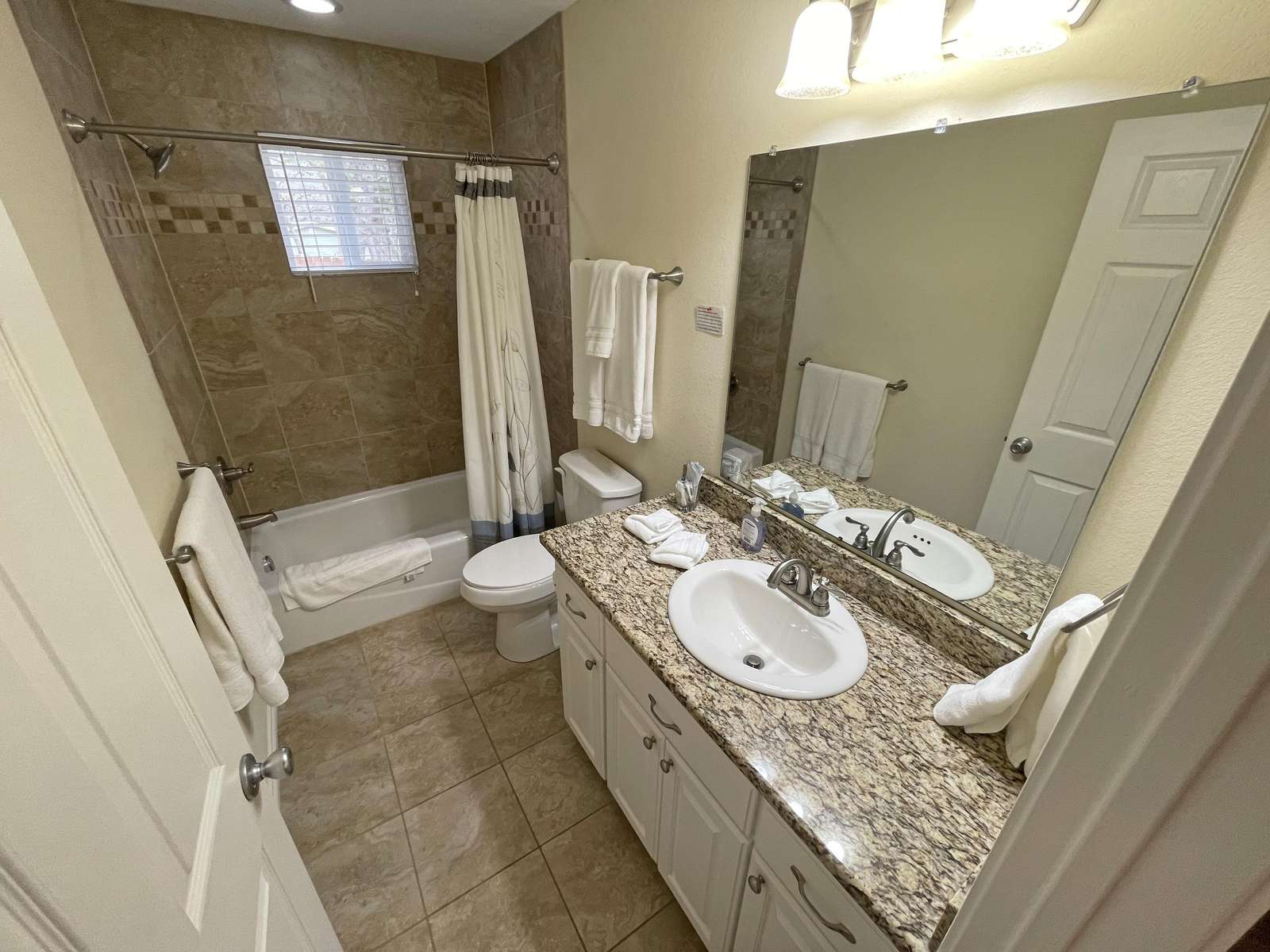 The main bathroom with granite counters and tile shower/tub unit.