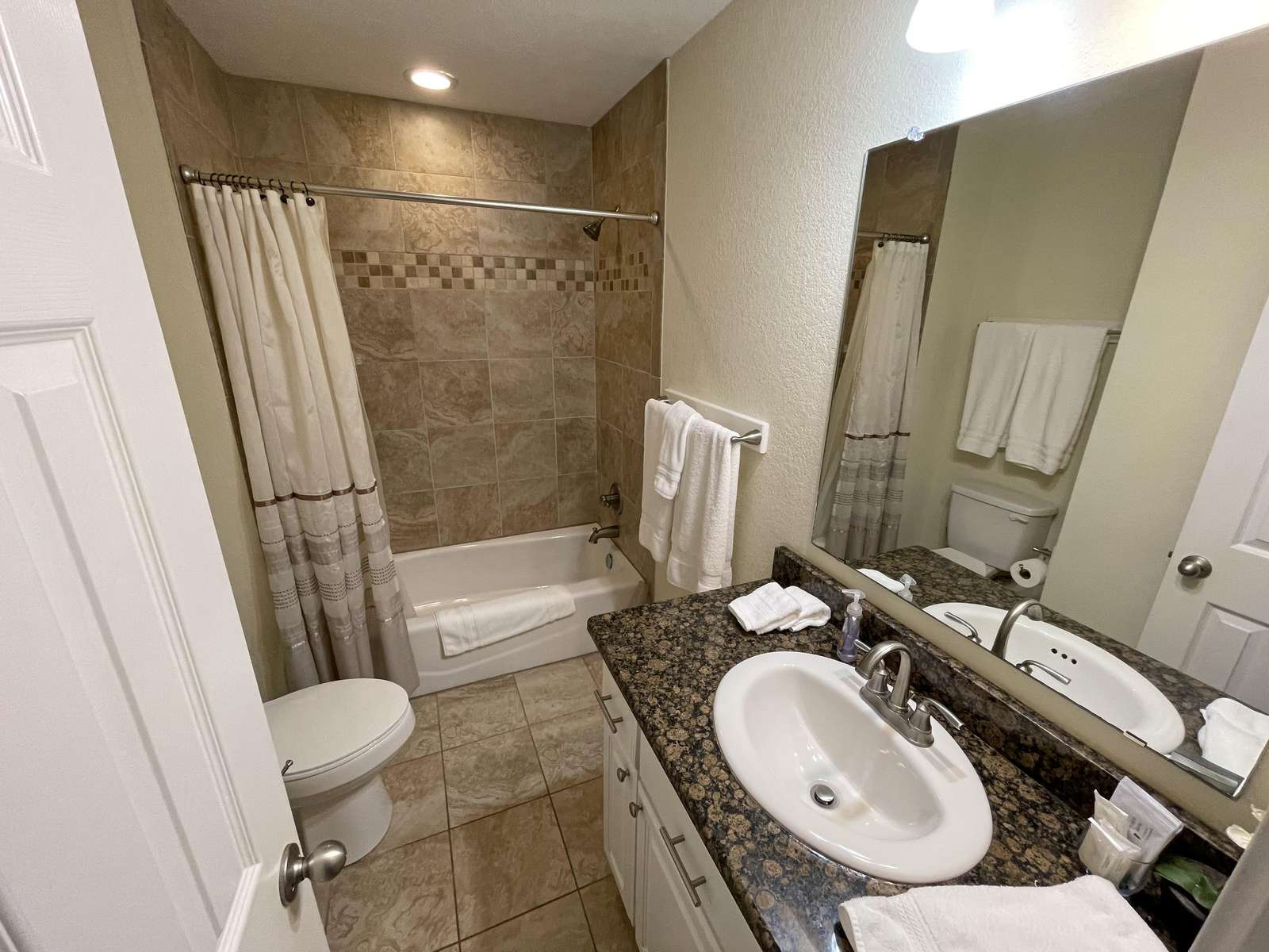 The upper level communal bathroom. All bathrooms are tiled with enamel tubs and granite counters throughout.