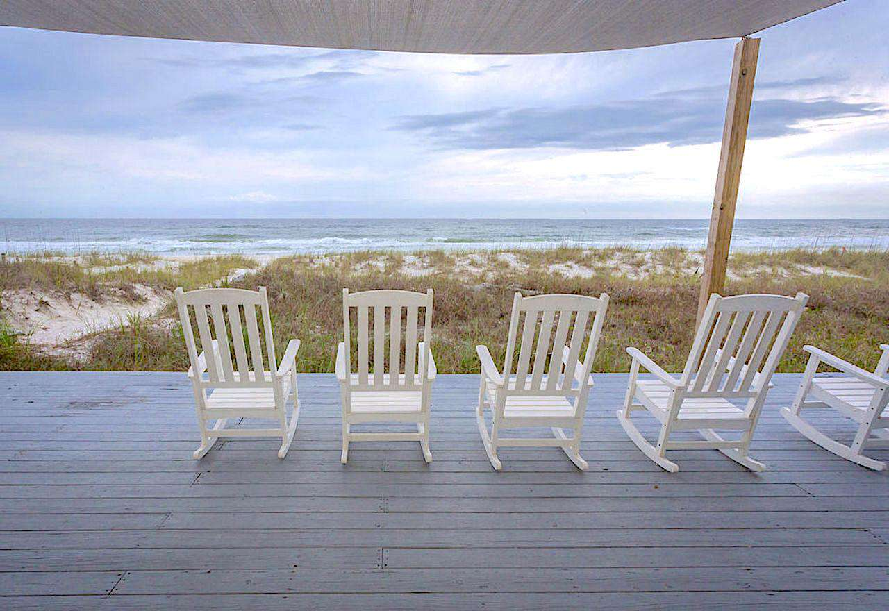Large back deck with rockers and sun screen overlooking the ocean