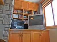 Oak entertainment center with TV, stereo, and books/movies thumb