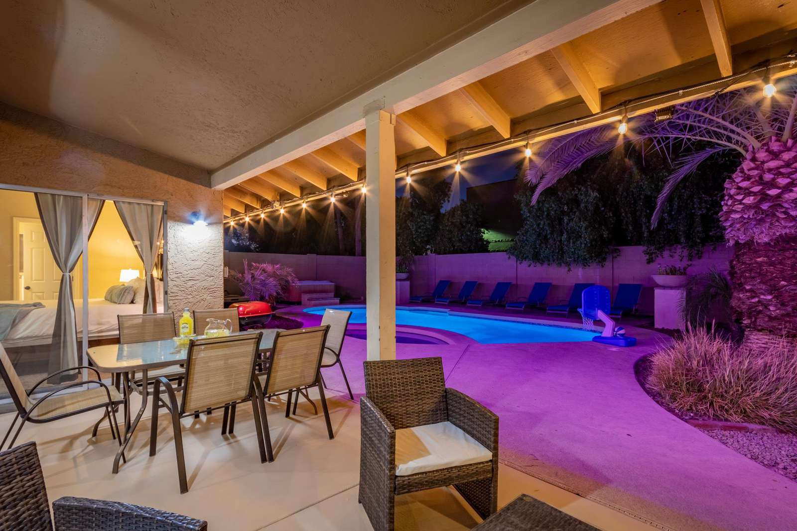 Covered Patio With Outdoor Dining Table, Seating Area and Gas Grill.