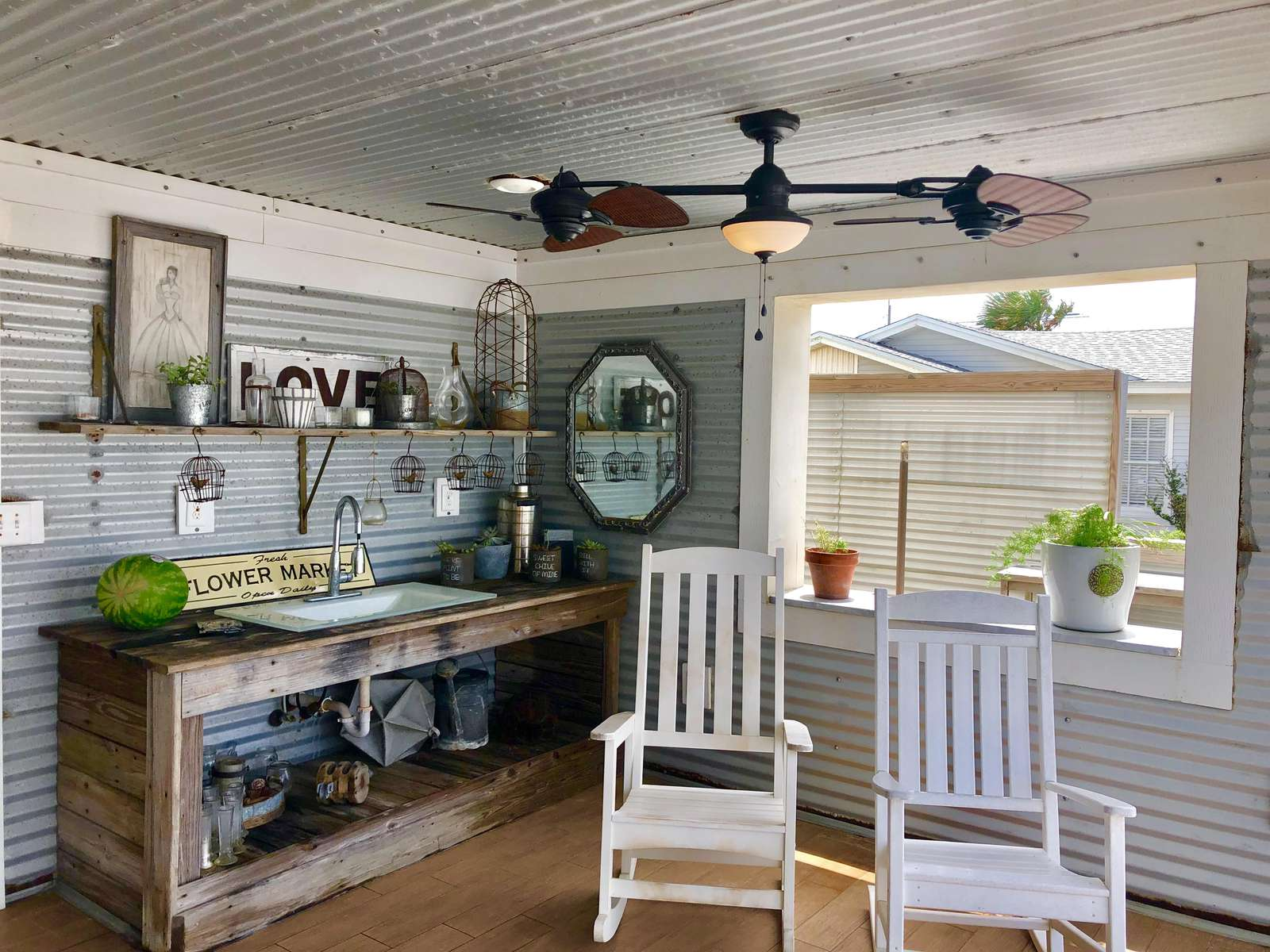 Logia on back deck with 4 rocking chairs, 2 ceilings fans, and sink