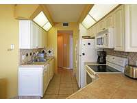 The kitchen opens into the living area. thumb