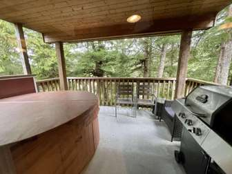 Covered deck with a hot tub, BBQ and deck chairs thumb