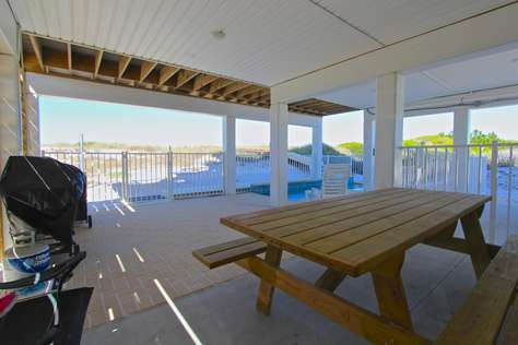 Covered pool deck with picnic table and gas/charcoal grills
