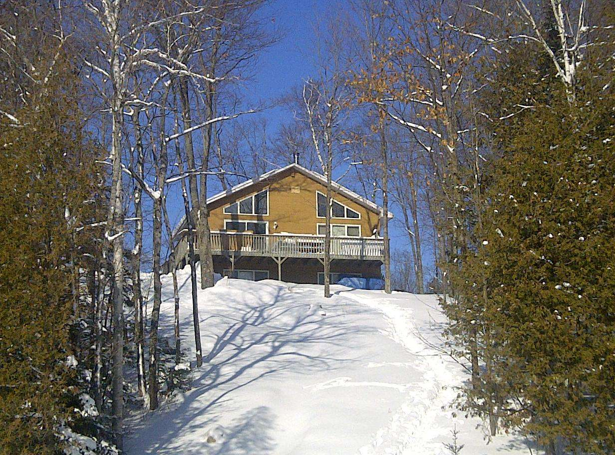 View of the cottage from the lake. Toboggan hill!
