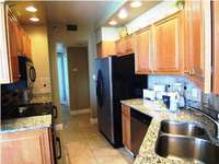 The kitchen features granite counter tops and stainless steel appliances. thumb
