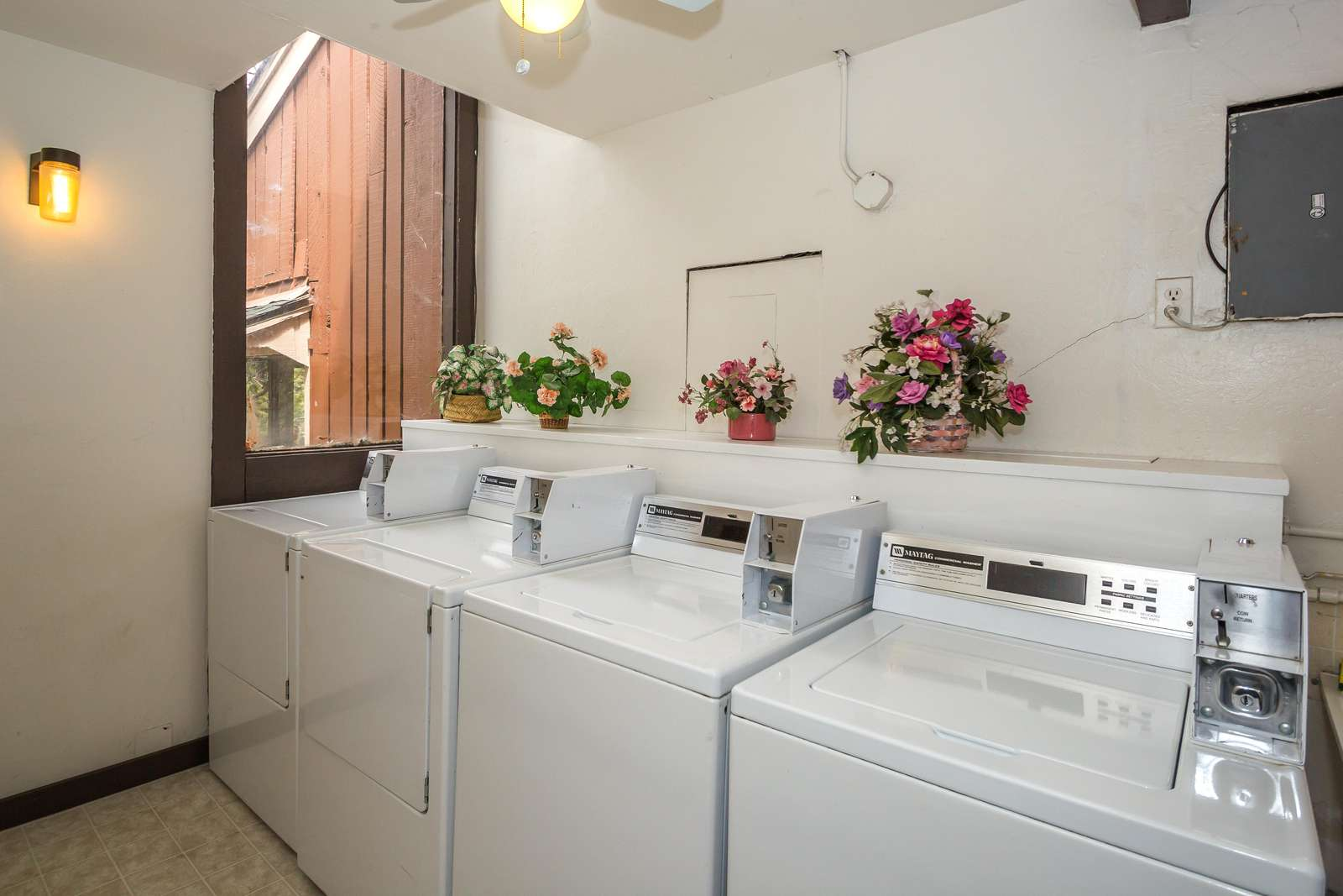 The public laundry room upstairs in the condominium building with coin operated machines.