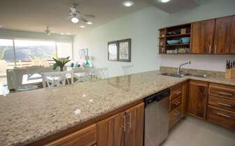 Granite countertops and stainless steel appliances in the fully equipped kitchen thumb