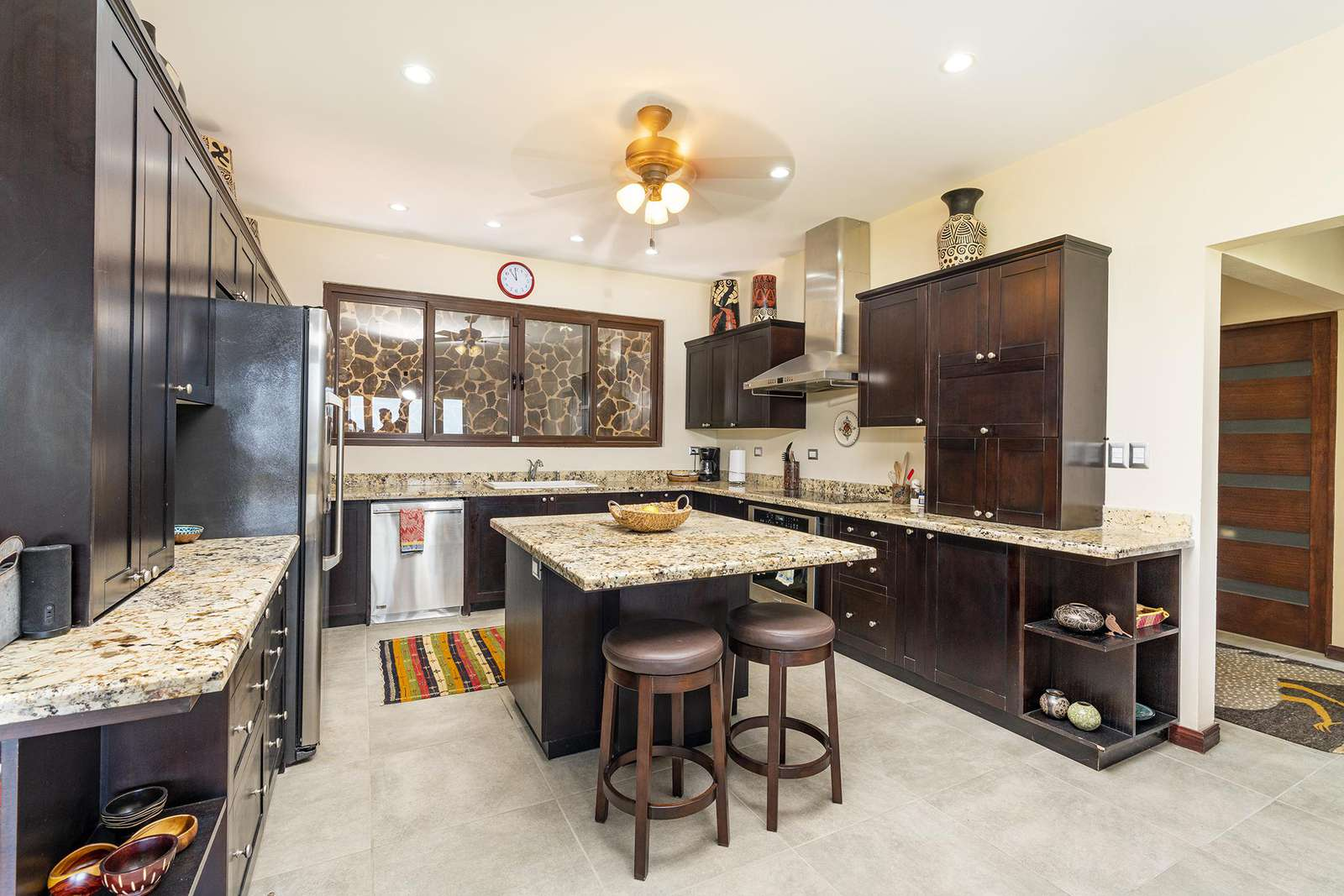 Gourmet kitchen, featuring wood cabinetry, granite countertops, stainless steel appliances, breakfast bar
