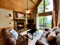 The Spacious Living Room Offers Incredible Views, Native Stone Fireplace, and a Wall of Glass to take in the Long Range Views thumb