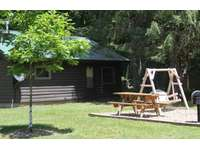 Twin Oaks Cabin showing back yard with swing thumb