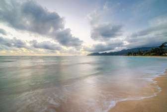view of beachfront at dawn on calm morning thumb