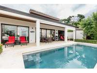 View of covered terrace area, pool, loungers, dining table and weber gas grill thumb