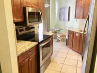 The recently renovated kitchen has new granite counter-tops and all new stainless steel appliances. thumb