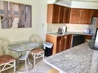 The kitchen flows into the living room with an eat-in bar area and balcony access. thumb