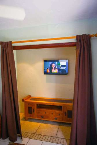 Flat screen smart TV iomn front of king size bed  thumb