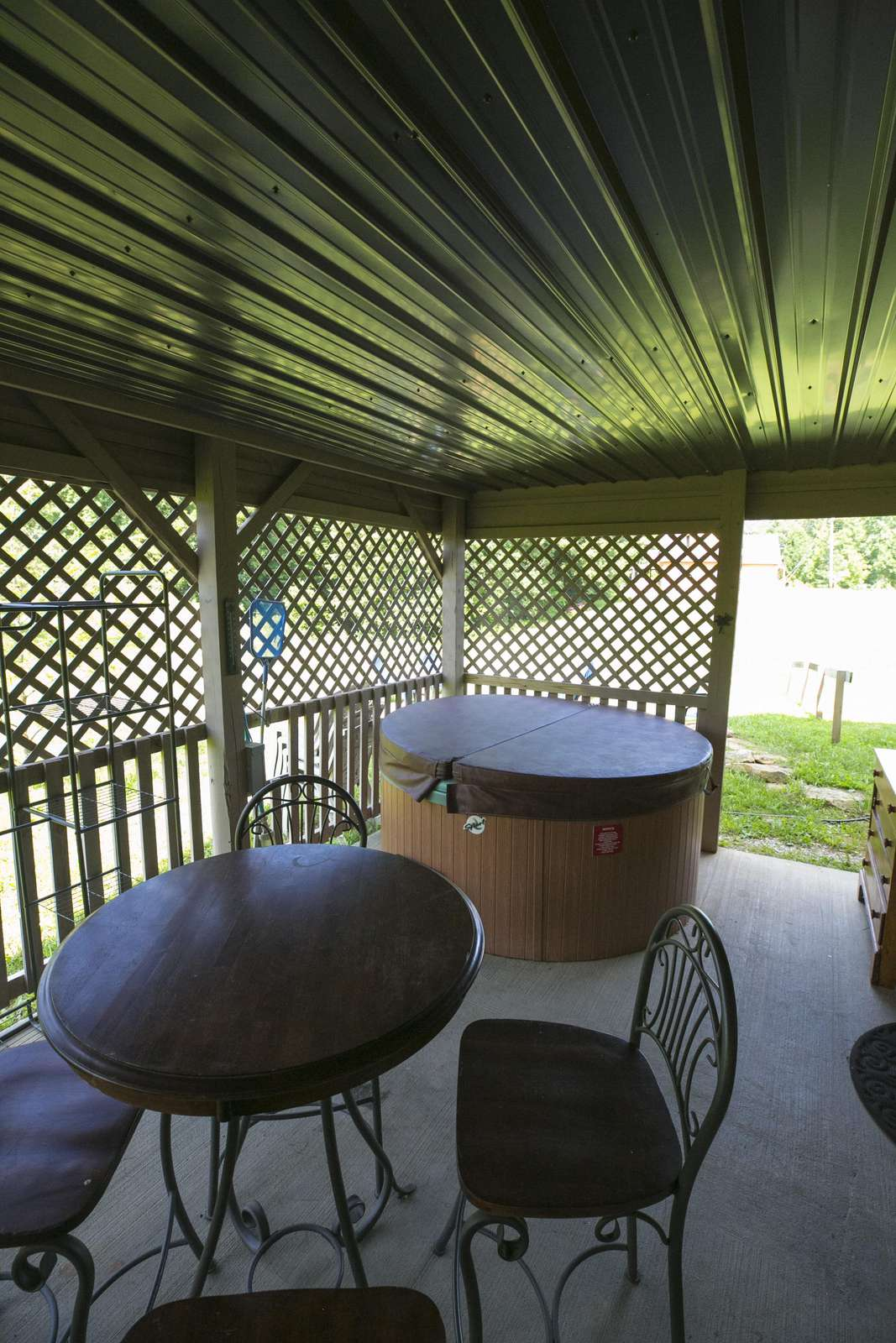 basement patio with hot tub and charcoal grill