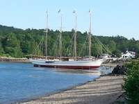 Schooner fitting out at low tide on beach across street. thumb