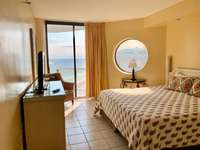 Master bedroom features a king bed, balcony access, great ocean views! thumb
