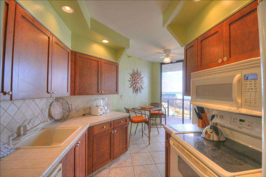 The large kitchen has views onto the balcony and beyond!