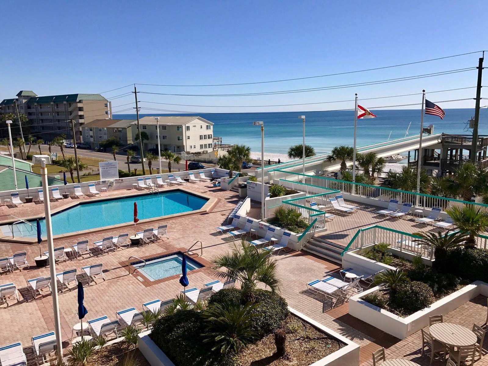 The pool deck features a large pool, 2 hot tubs, kiddie pool, tiki bar, saunas, and beach road walk over.
