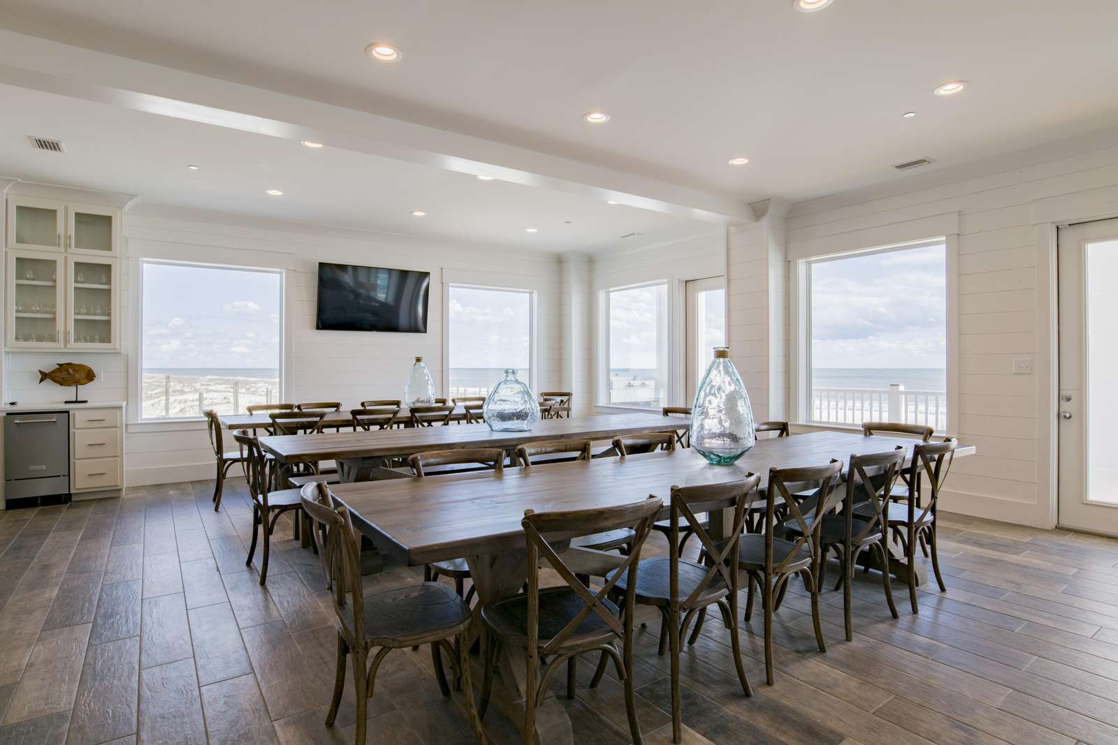 Dining Area with 3, 12 ft dining tables and 65 inch flat screen.