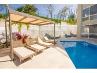 Relax poolside under the shaded palapa thumb