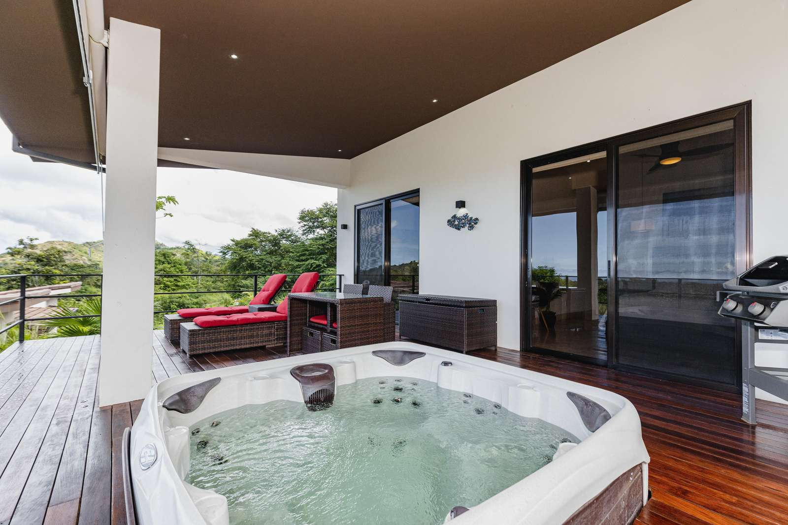 Private covered deck, jacuzzi, loungers and dining area with Weber BBQ grill
