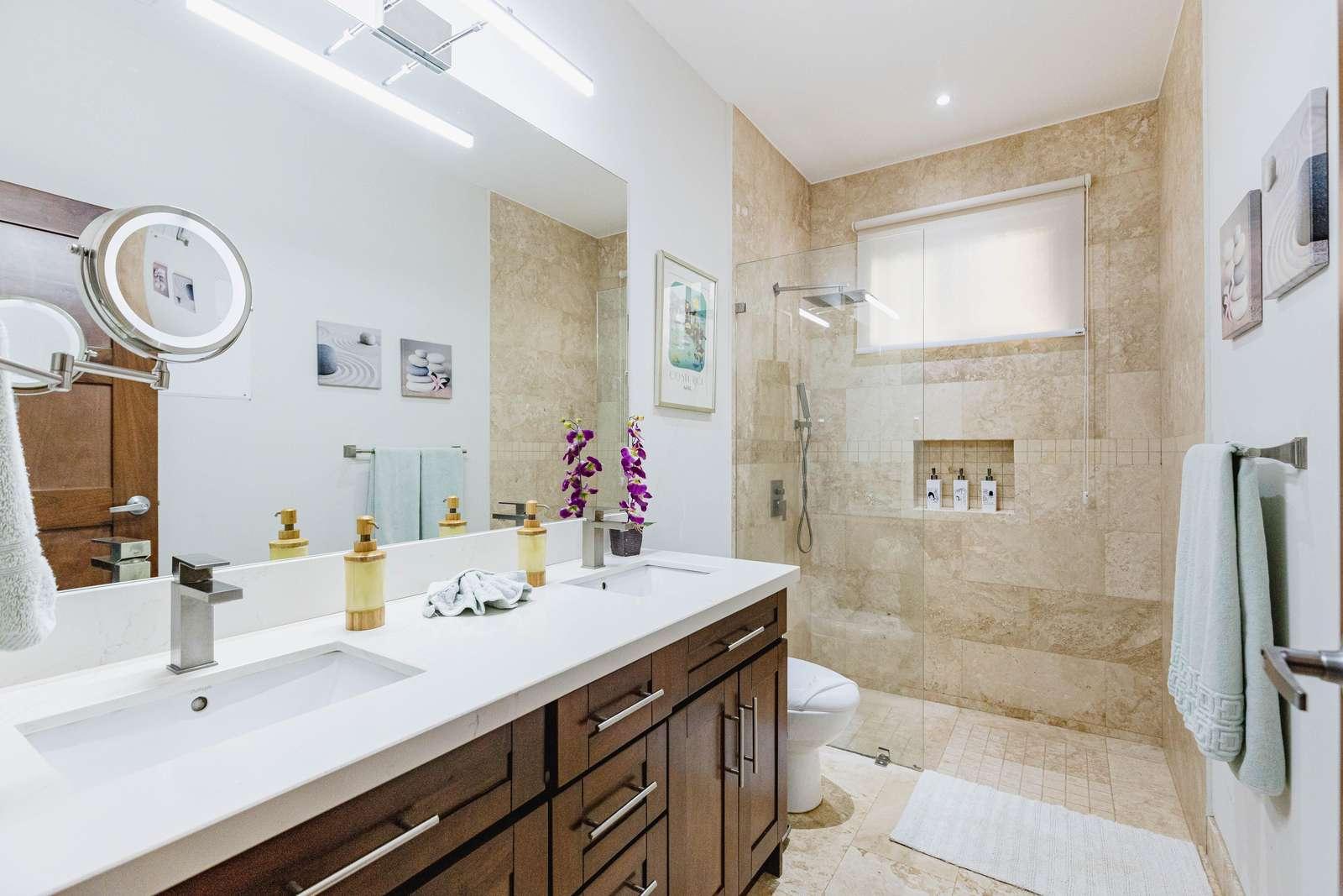 Full private bathroom, dual vanity, quartz countertops, walk in shower, travertine flooring