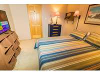 Full-sized bed in second bedroom; chest of drawers and closet for storage. thumb