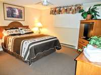 Queen-sized bed in master bedroom - ample room to spread out. Entertainment center and chest of drawers. thumb
