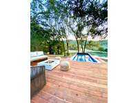Large lounging deck overlooking pool and pond thumb