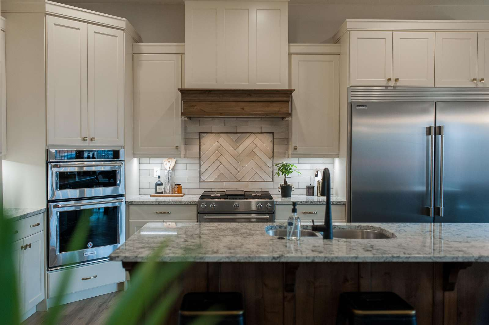Grand kitchen features a sub-zero style refrigerator, gas range, oven, icemaker