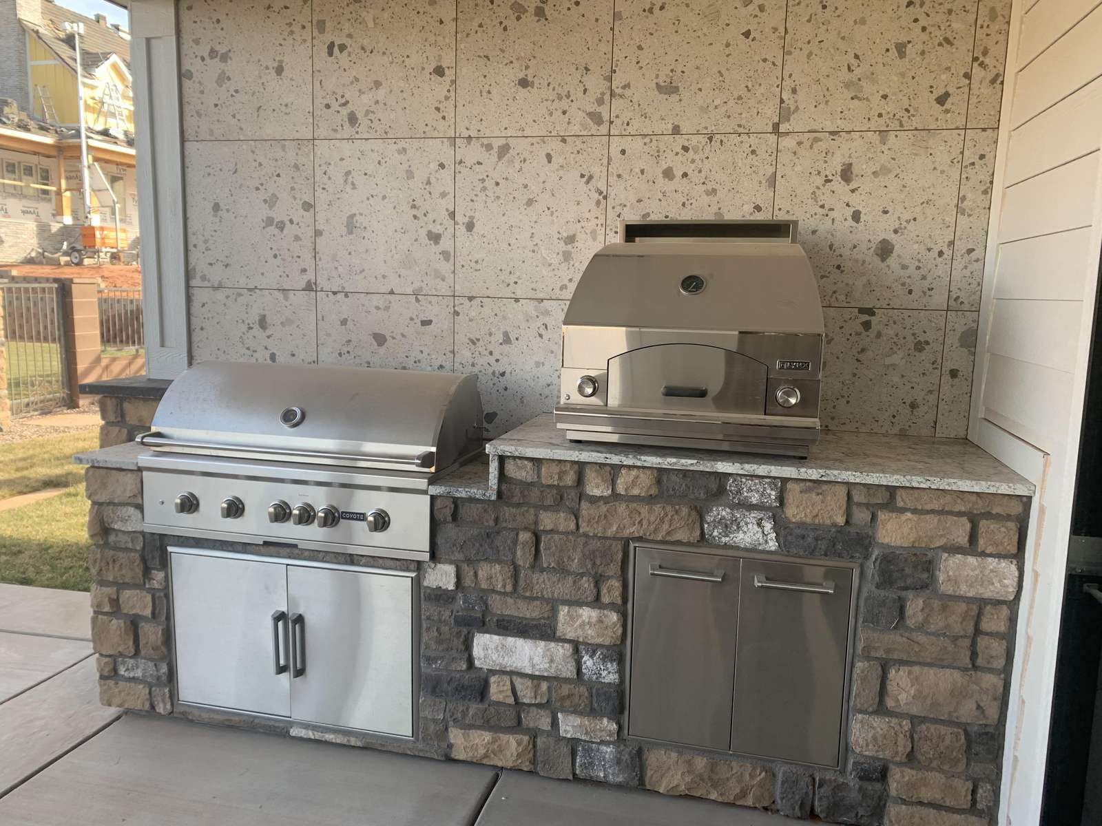 outdoor kitchen includes a pergola, outdoor seating, gas grill, and pizza oven