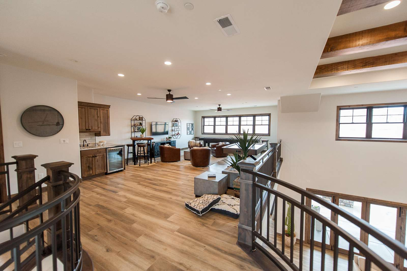 Game room loft includes shuffleboard, fooseball table, and entertainment console