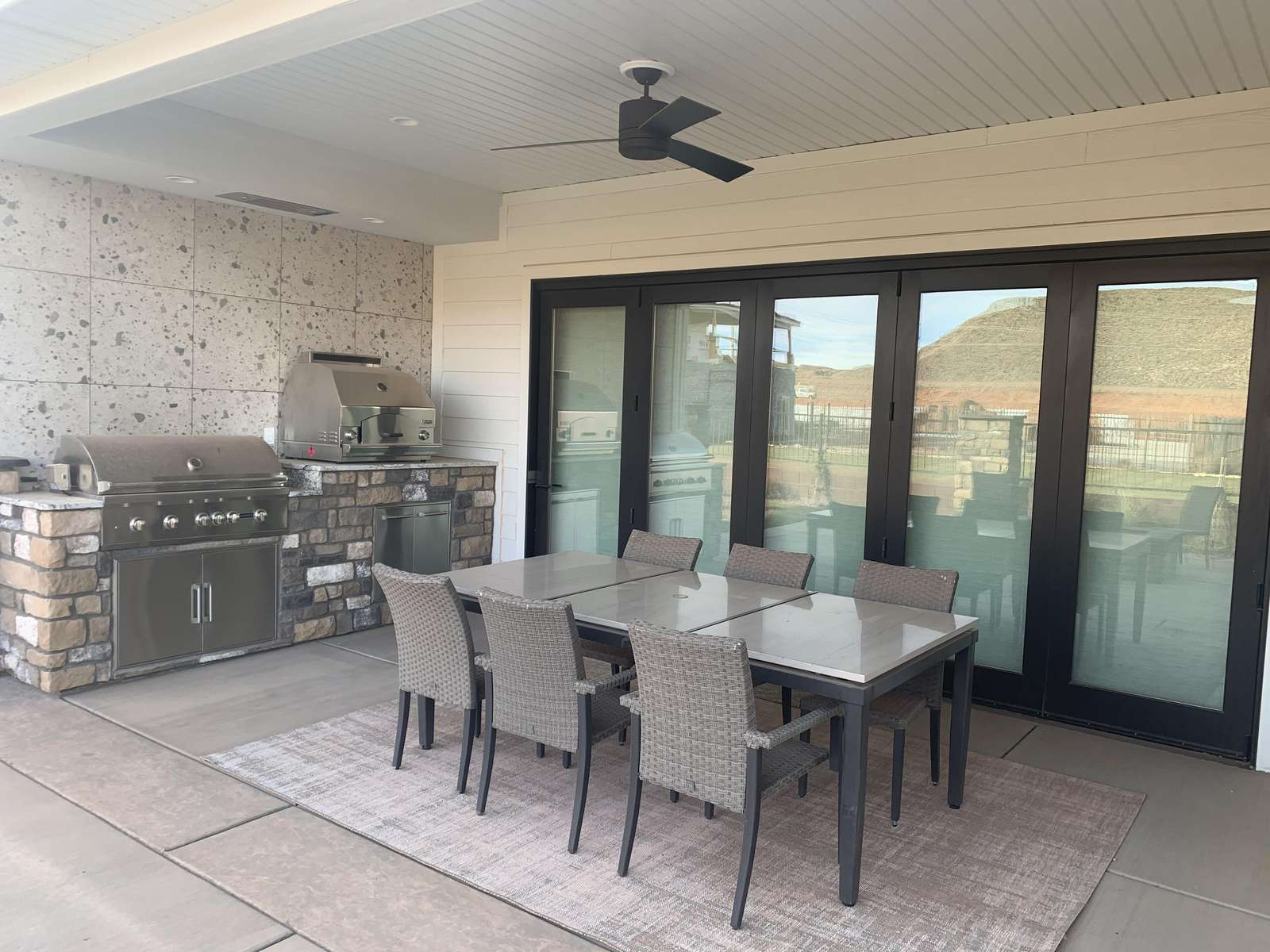 Outdoor kitchen space includes gas grill and pizza oven