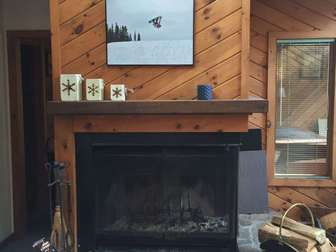 Family room fireplace, wood supplied to your front door, and hot tub room visible in room behind fireplace. thumb