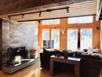 Step into sunlight, wood beams, and an inviting family room with dramatic fireplace. thumb