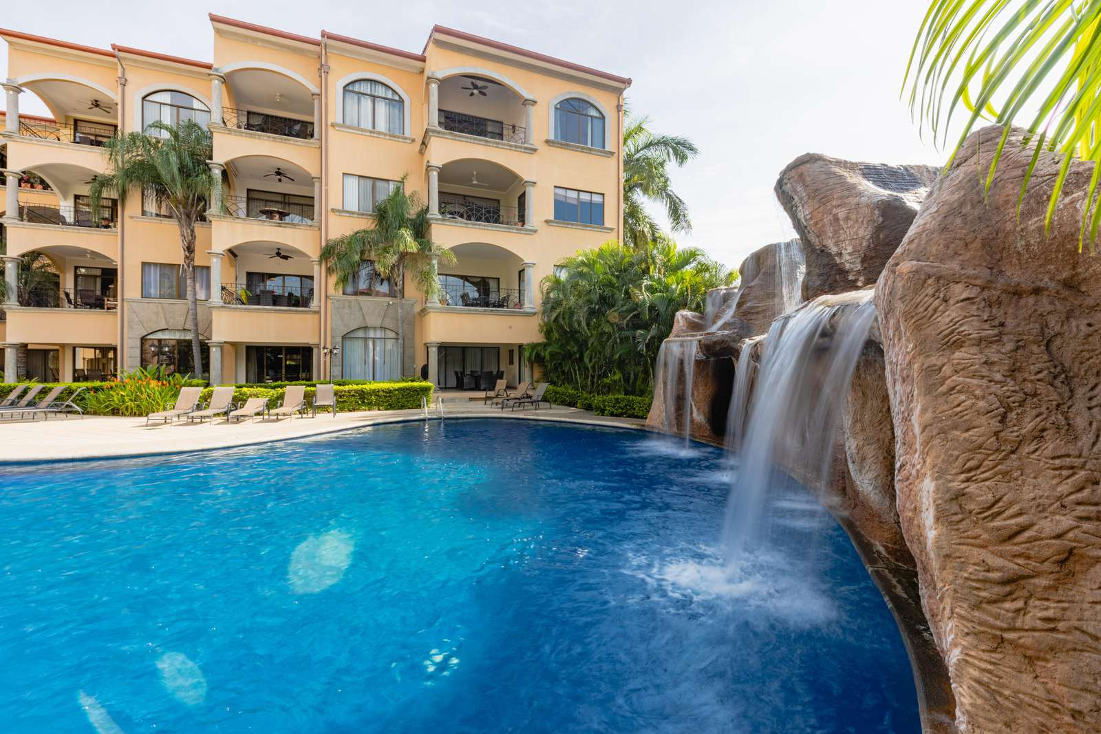 Resort style pool with cascading waterfall feature