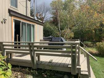 Deck with gas grill and view of golf course thumb