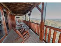 Main level balcony where you can relax with a cup of coffee in our aspen log rocking chairs thumb