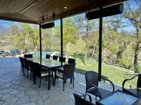 Outdoor patio and dining area overlooking pool and grassy areas thumb