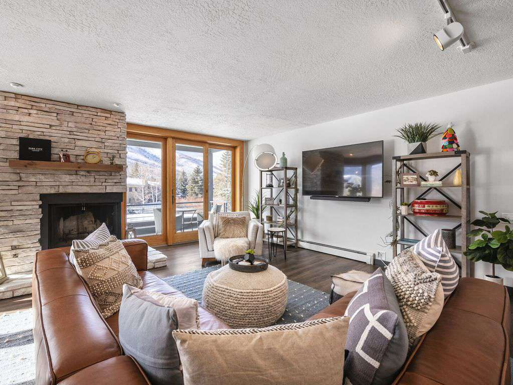 Great room has a wood burning fireplace and giant view windows with wrap around deck