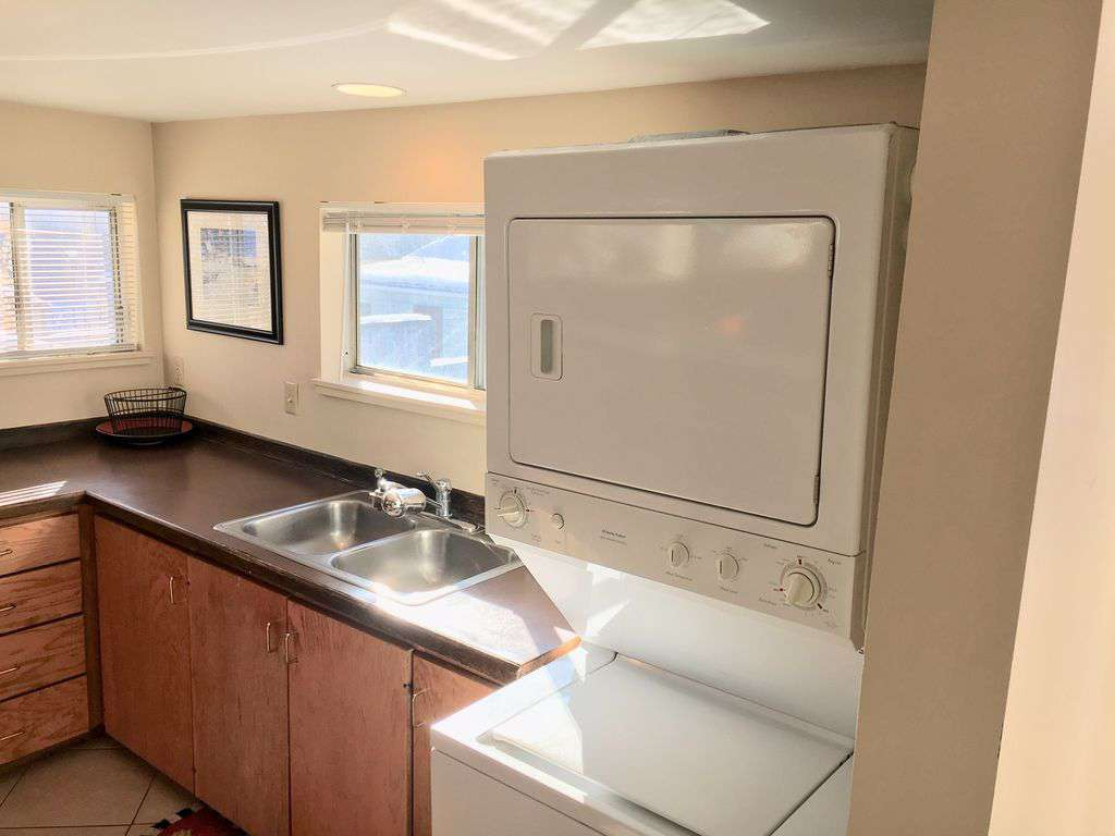 Second level kitchenette with sink, microwave and full size fridge and washer and dryer