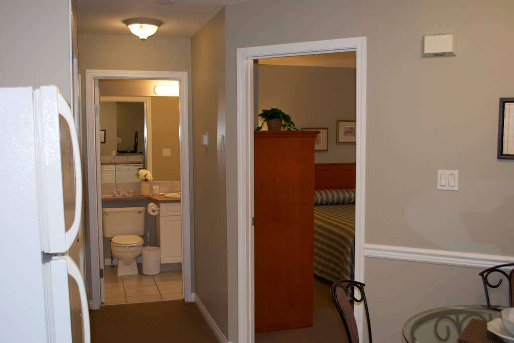 First bedroom with single queen bed and attached bathroom. The bedroom has a separate door to the bathroom than the one shown.