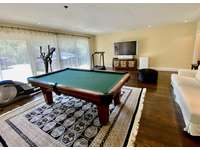 Lower level game room w/ pool table, large TV and exercise equipment thumb
