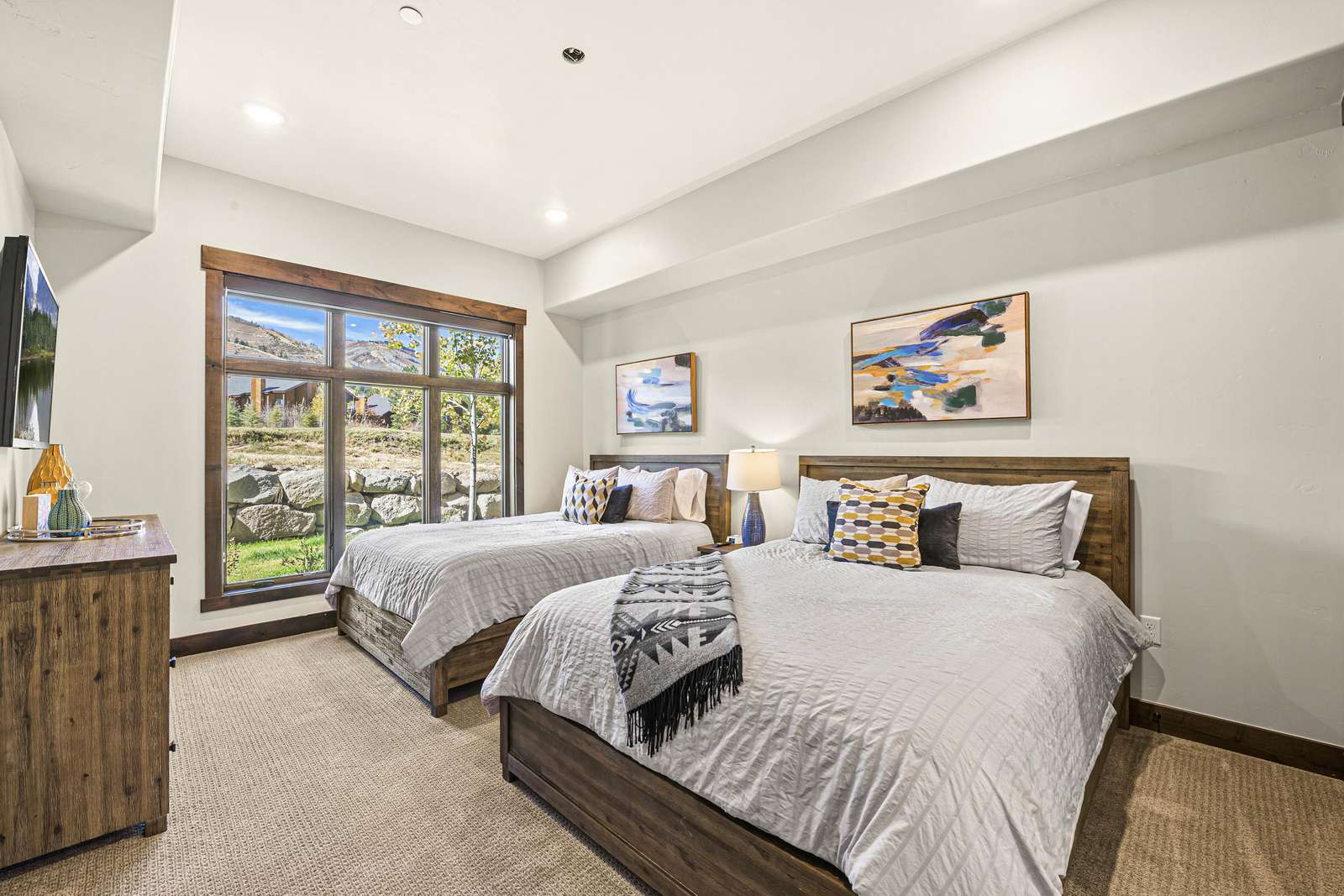 Comfortable guest bedroom with TV and two queen beds